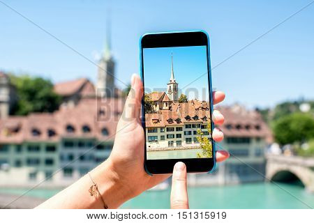 Photographing with smart phone the old town of Bern city with Nydegg church and river in Switzerland