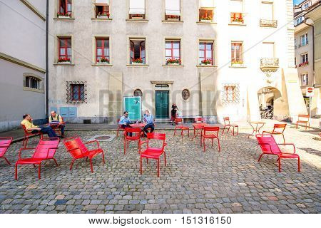 Bern, Switzerland - June 24, 2016: People sit on the popular red public chairs on the central square in Bern old town in Switzerland.