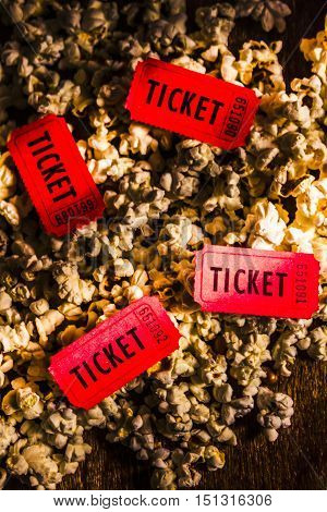 Top view of scattered red theater movie tickets on buttered crunchy crispy popcorn cinema entry