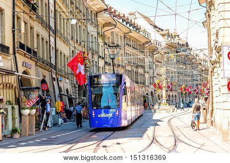 Bern, Switzerland - June 24, 2016: Street view on Kramgasse with modern blue tram in the old town of Bern city. Kramgasse is a popular shopping street and medieval city centre of Bern, Switzerland.