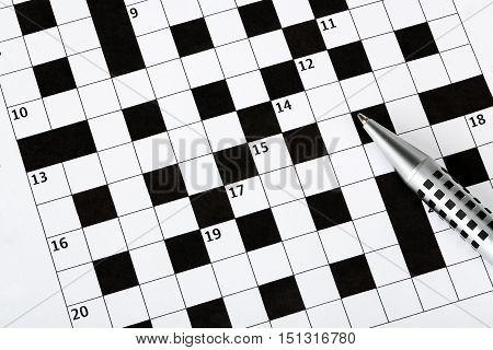 closeup of pen on blank crossword puzzle