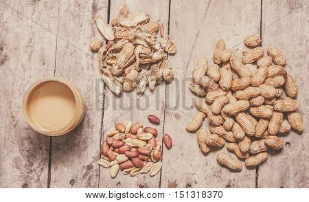 Pile of fresh whole peanuts shells raw nuts and peanut butter in a jar conceptual of production and preparation of the final product overhead view