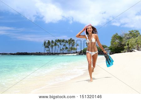 Bikini woman happy having fun running on white sand beach with fins and snorkeling gear. Tropical vacation girl relaxing in summer travel destination paradise doing ocean swimming activity.