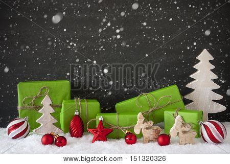 Green Gifts Or Presents With Christmas Decoration Like Tree, Moose Or Red Christmas Tree Ball. Black Cement Wall As Background With Snow. Christmas Greeting Card With Snowflakes