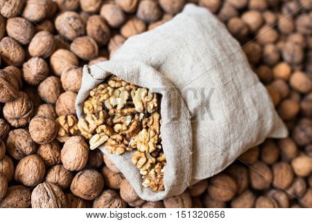 Walnuts kernels in the small linen sack on the pile of walnuts in shell