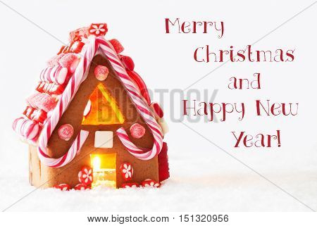 Gingerbread House In Snowy Scenery As Christmas Decoration With White Background. Candlelight For Romantic Atmosphere. English Text Merry Christmas And Happy New Year