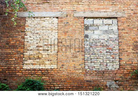 Brick wall with two window openings laid with bricks.