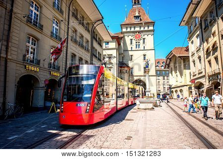 Bern, Switzerland - June 24, 2016: Street view on Kramgasse with red tram in the old town of Bern city. Kramgasse is a popular shopping street and medieval city centre of Bern, Switzerland.