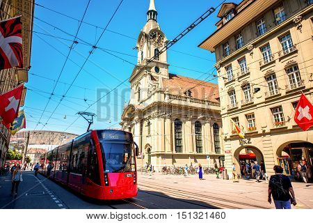 Bern, Switzerland - June 24, 2016: Street view with red tram and Holy Spirit church in Bern city in Switzerland.
