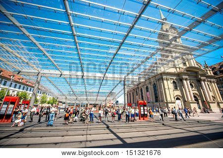 Bern, Switzerland - June 24, 2016: Modern tram station with glass construction and view on Holy Spirit church in Bern city in Switzerland.