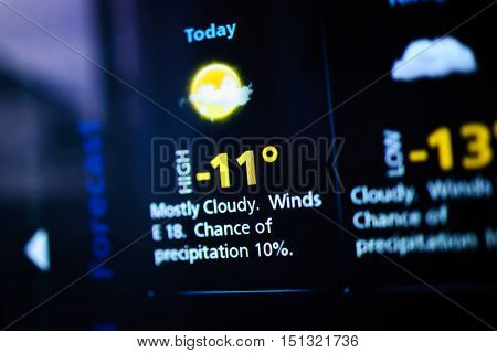 Weather forecast interface on a modern digital display showing cold weather for the next days. Tilt-shift lens used to outline the cold -13 symbols.