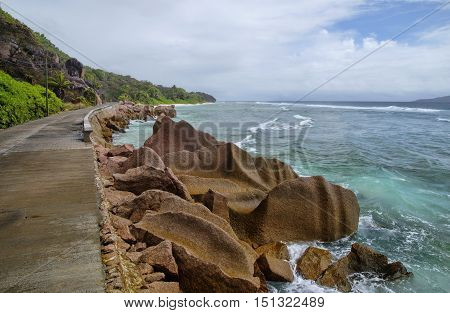 Low Tide At The Wild East Coast Of La Digue, Seychelles With The Only Road In The Foreground