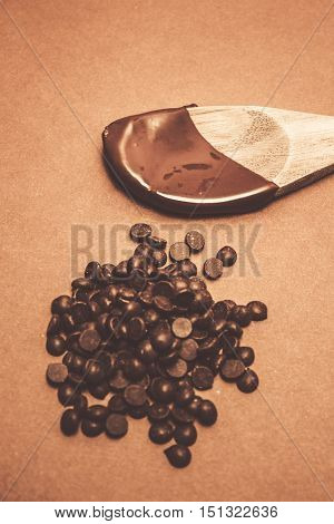 Brown food photography on a wooden spoon covered in melted cookery chocolate next to dark choc pieces. Baking desserts