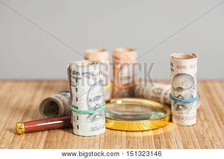 Rolls of Indian Currency Rupee Notes with magnifying glass on wooden background