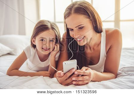 Beautiful young woman and her charming little daughter in earphones are listening to music using a smart phone and smiling while lying in bed at home