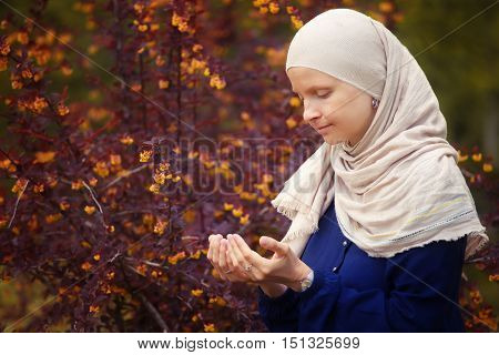 Young muslim woman praying in the park