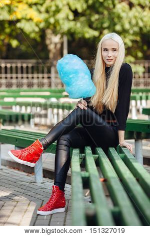 Young Stlylish Sporty Blond Beautiful Teen Girl With Cyan-blue Candy-floss Sitting Crossed Legs At P