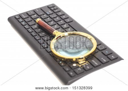 Magnifying Glass on black keyboard isolated on white