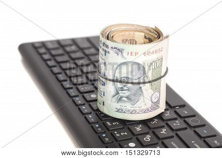 Roll of Indian Currency Rupee Notes on computer keyboard isolated on white