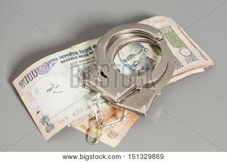 Indian Currency Rupee Notes and Handcuffs on gray background