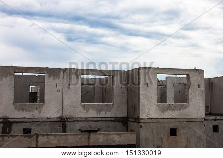 Unfinished grey concrete building in the construction site.
