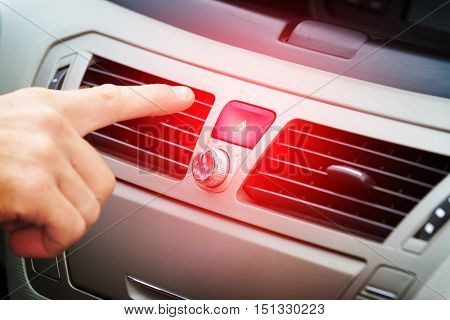 Driver pressing red triangle car hazard warning button