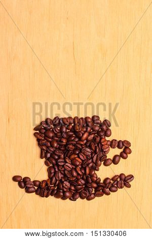 Roasted coffee beans placed in the shape of cup and saucer on wooden surface background copy space text area