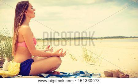 Woman Doing Yoga On Sandy Beach.