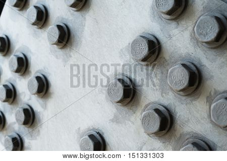 Gray metal surface with hexagonal bolt heads.