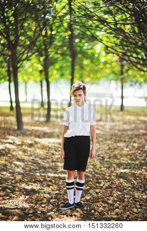 Portrait in full growth the young girl slender brunette with Dyed locks of hair in a white blouse and black skirt in autumn park.