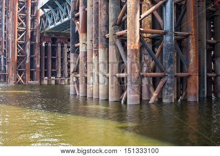 Bridge construction. Rusty metal piers of the unfinished bridge across the Dnieper in Kyiv (Ukraine).