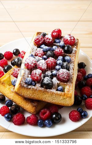 Homemade breakfast Belgian waffles with blueberry and raspberry. Breakfast waffles with fresh berries.