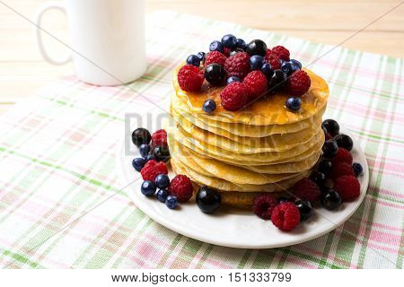 Breakfast pancakes with honey and fresh berries and coffee mug. Homemade pancakes served with blueberry raspberry and blackcurrant.