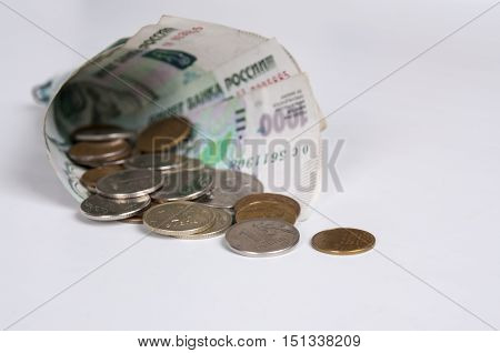 Denominations folded bags with coins on white background
