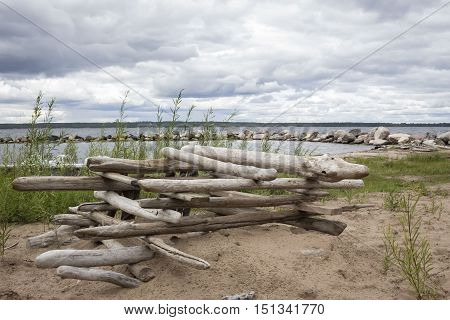 horizontal image of logs piled up on sand in a square formation next to a big lake in the summer time.