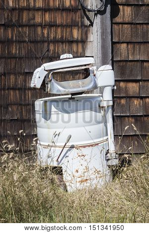 vertical image of an old fashioned antique wringer washer sitting in dead grass outside the home.