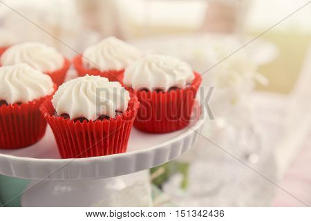 Red velvet cupcakes on white cake stand toning