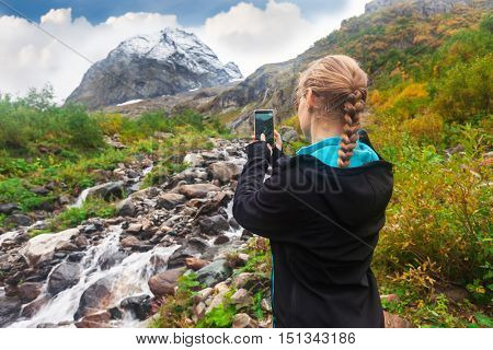 woman taking a photo of mountain on smartphone