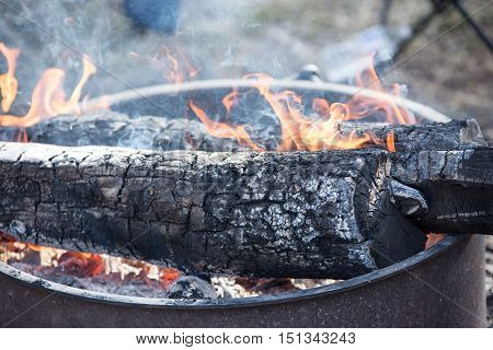 Campfire with wood and hot flames in a fire pit.