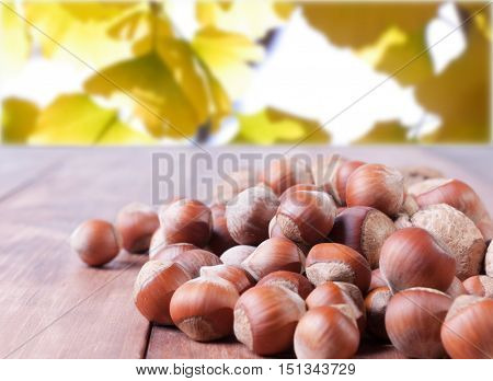Mix of nuts on wooden background. Background from the leaves blurred
