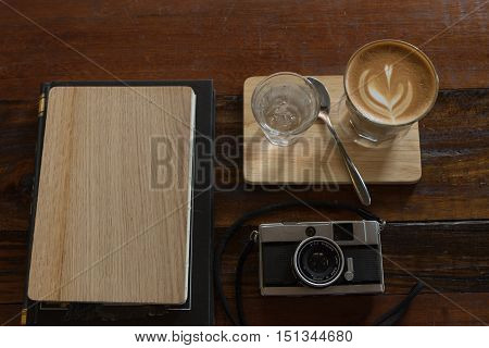 hot fresh coffee in see through glass water glass retro camera and wooden notebook on wooden tray and table at coffee time / hot fresh coffee and camera