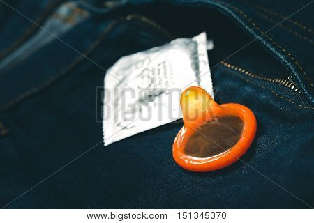Condom on jeans. Safe sex concept. vintage style processed.