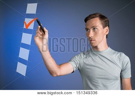 Young man t-shirt checking on checklist box. Blue background.