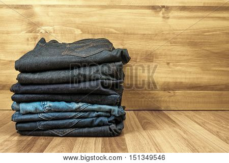 Blue Jeans On A Brown Wooden Background And Blue Jeans Denim Collection Jeans Stacked