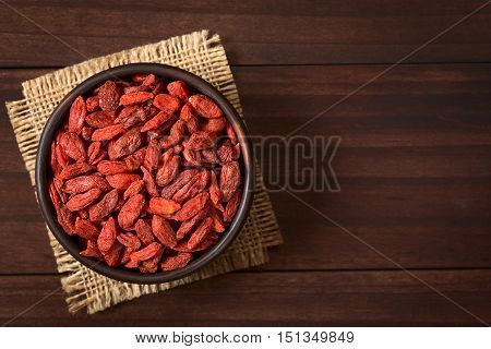 Dried gojis or wolfberries in small bowl photographed overhead on dark wood with natural light (Selective Focus Focus on the top of the berries)
