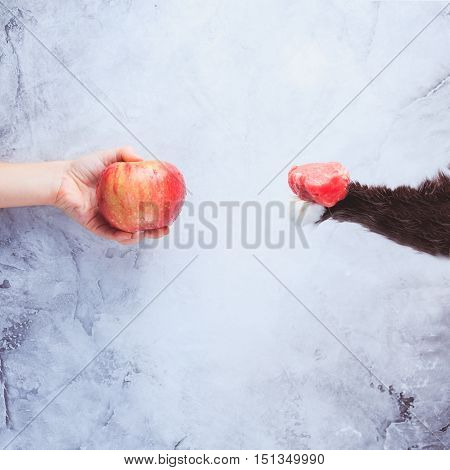 Go Vegan! Concept Of Veganism. Vegan Diet. Human Hand With Apple And Cat Paw With Meat.