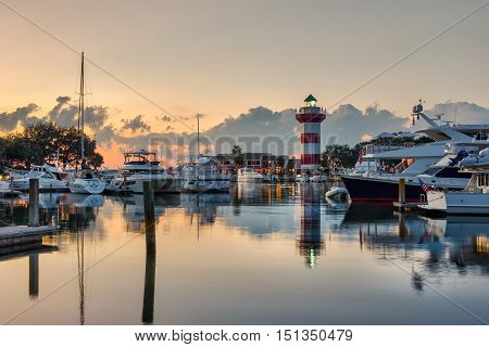 Hilton Head Island and its iconic lighthouse lit up at sunset with a glass like water with reflections of boats and lighthouse.