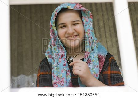 Portrait of Attractive Cute Muslim Girl winking directly at the Camera. Positive Human Emotion Facial Expression Body Language. Funny Girl Touching Heart Shape Necklace