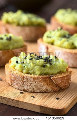 Bread slices with green pea and parsley spread garnished with black sesame seeds served on wooden board photographed with natural light (Selective Focus Focus on the front of the spread on the first bread)