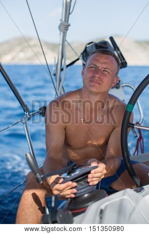 A man the skipper on his yacht pulls the rope during drives the sailing boat.